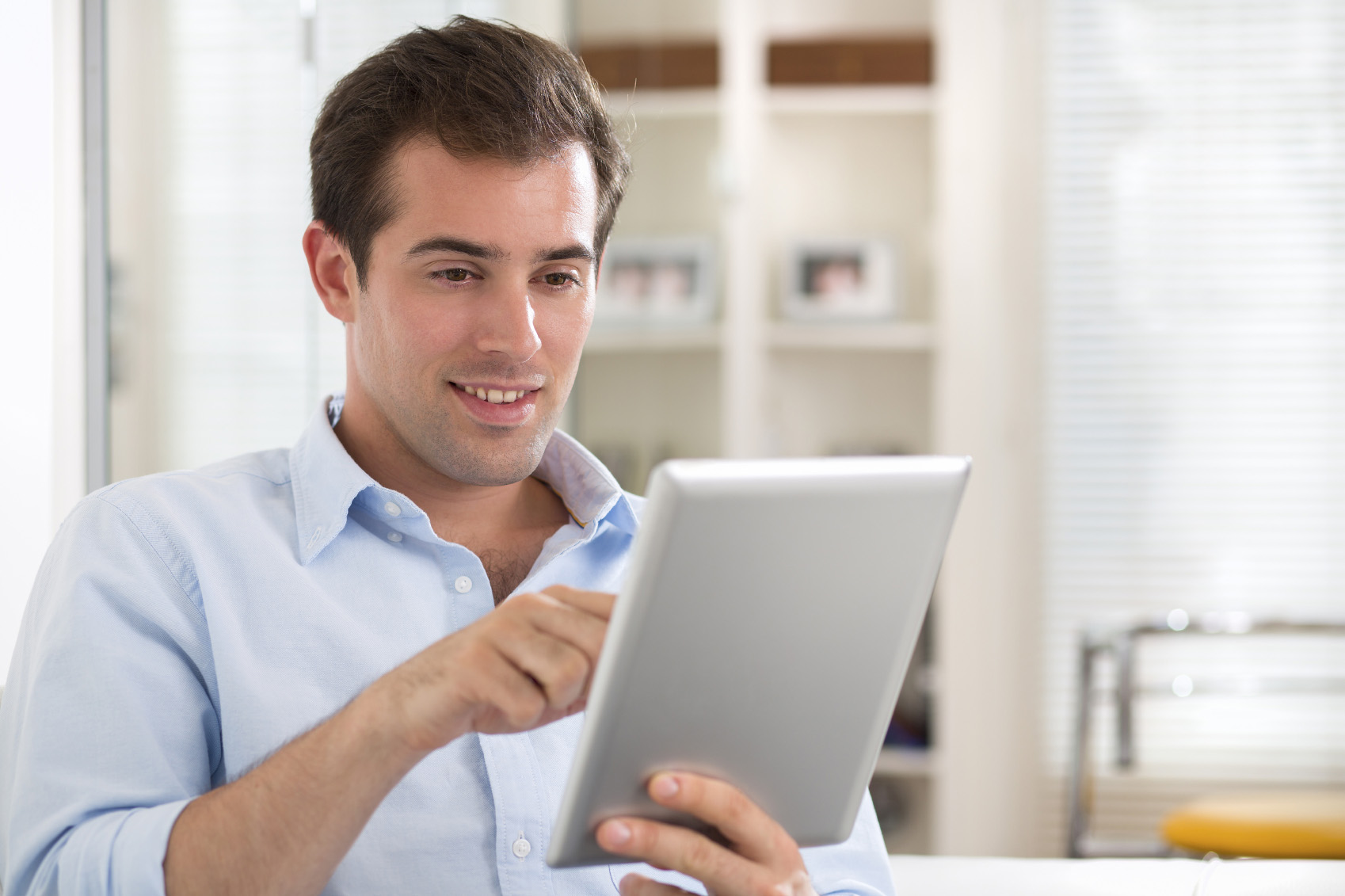 Man using tablet pc on couch at home